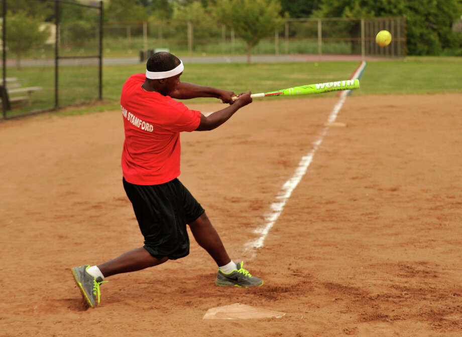Claudel Larose, batting for the Mayor's office, belts a home run during the Mayor's office versus Board of Representatives' annual softball game at Boccuzzi Park in Stamford on Monday, Aug. 19, 2013. The Board of Reps won, 11-10. Photo: Jason Rearick / Stamford Advocate