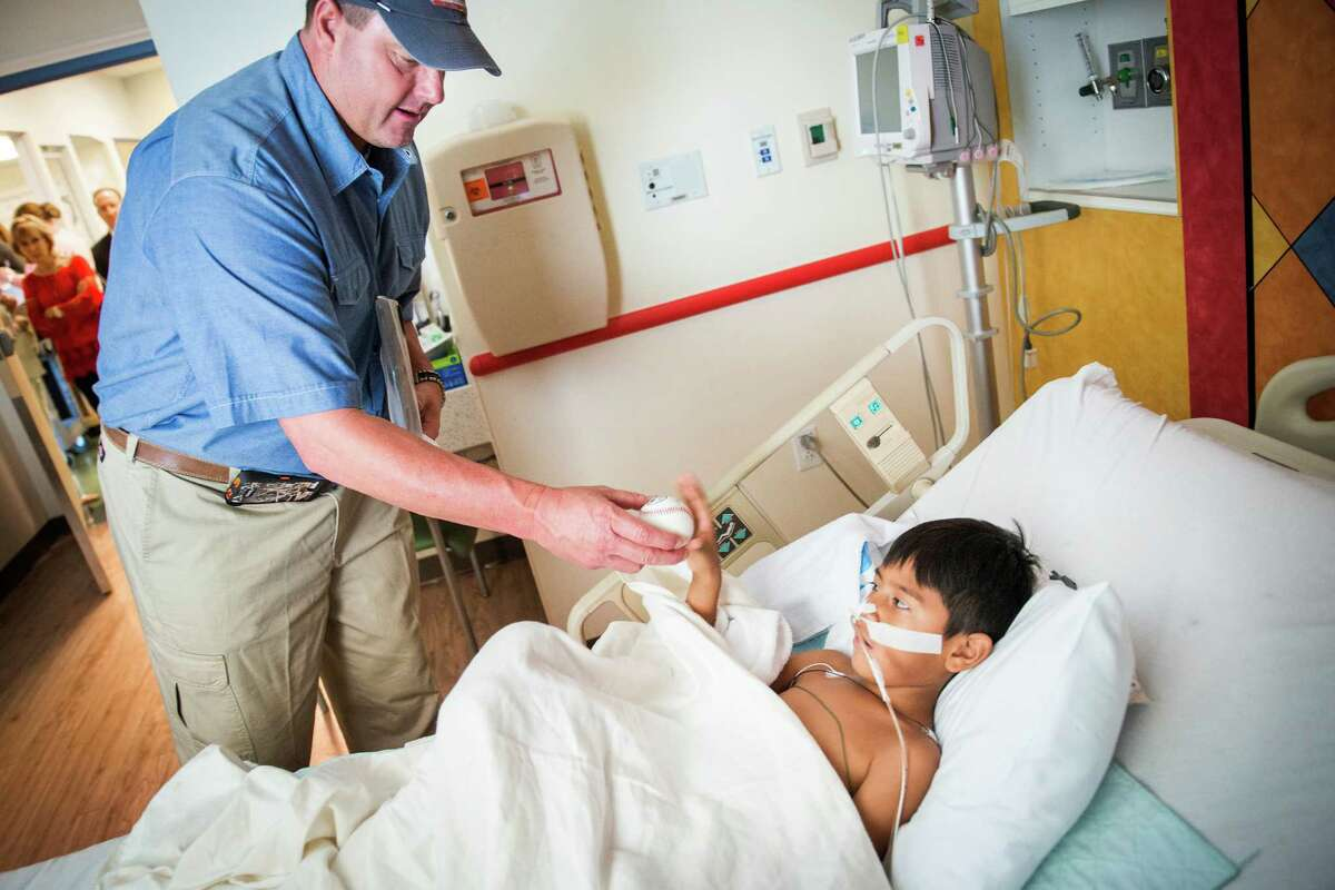 Roger Clemens gives an autographed baseball to Giovanny Silva, 6, a patient at Children's Memorial Hermann Hospital on Monday, Aug. 19, 2013, in Houston. The former Major League Baseball pitcher visited pediatric patients in the dedicated Roger & Debbie Clemens Pediatric Wing at the hospital.