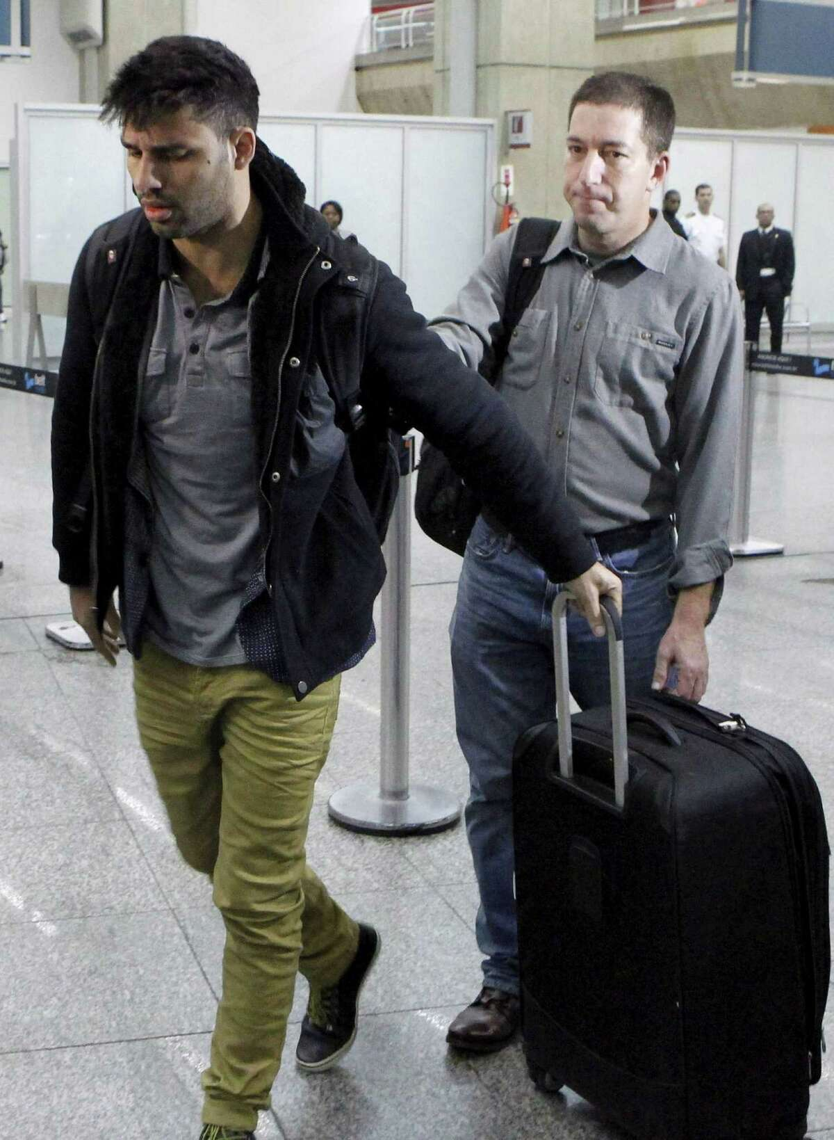 David Miranda (left) arrives in Rio de Janeiro after being detained as he passed through London from Berlin.