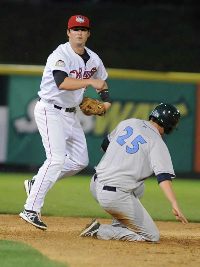 Tri-City ValleyCats second baseman Ryan Dineen turns a double play while Ryon Healy of the Vermont Lake Monsters hits the dirt during a baseball game at Joe Bruno Stadium on Monday, Aug. 19, 2013 in Troy, N.Y. (Lori Van Buren / Times Union) Photo: Lori Van Buren / 00023557A