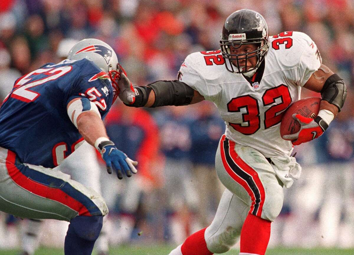 FILE--Atlanta Falcons running back Jamal Anderson (32) straight-arms New England Patriots linebacker Ted Johnson (52) in route to a second quarter touchdown at Foxboro Stadium in Foxboro, Mass., in this Nov. 8, 1998 photo. The Falcons (11-2) need a win to stay on Sunday, Dec. 13, 1998 against the New Orleans Saints to ahead of San Francisco in the NFC West and hold on to a first-round playoff bye. (AP Photo/Winslow Townson)