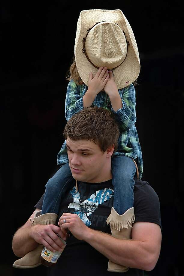 Madison Strohl, 4, of Albrightsville, Pa., playfully takes off her father Matthew's hat on Monday, Aug. 19, 2013 during the 156th Harford fair held in Harford, Pa.  (AP Photo /The Scranton Times-Tribune, Butch Comegys) Photo: Butch Comegys, Associated Press