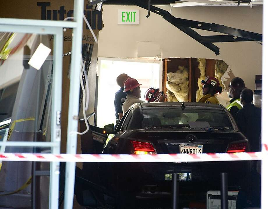 Authorities assess the damage at the scene where a car crashed into the Tutoring Club in Fountain Valley, Calif., on Monday, Aug. 19, 2013. Police say a 76-year-old man drove his car into the tutoring club, injuring five people, including two who were trapped underneath the vehicle. (AP Photo/The Orange County Register, Sam Gangwer) Photo: Sam Gangwer, Associated Press