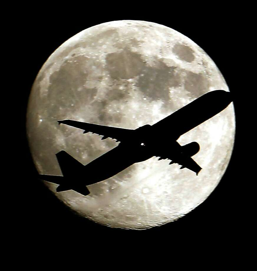 A airlines jet plane approaching Los Angeles International Airport  crosses the moon as seen from Palm Park in Whittier, Ca., on Monday Aug. 19, 2013. (AP Photo/Nick Ut) Photo: Nick Ut, Associated Press