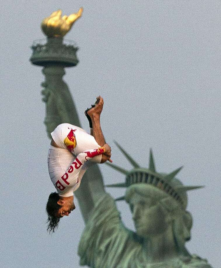 Colombian athlete Orlando Duque performs a 75-foot tuck dive after tumbling from a helicopter beside the Statue of Liberty in New York harbor, Monday, August 19, 2013, in New York.  Duque performed the stunt  to promote the fifth stop of the Red Bull Cliff Diving World Series this weekend in Boston. (AP Photo/Dean Treml, Red Bull) Photo: Dean Treml, Associated Press