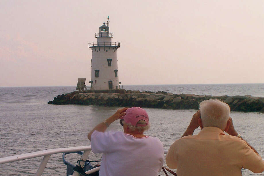 A group of seniors take in the beauty of the Saybrook Breakwater Lighthouse in Old Saybrook during a tour of Connecticut lighthouses. In August 2013, the lighthouse was sold by the federal government for $340,000. Photo: Contributed Photo, ST / Norwalk Citizen