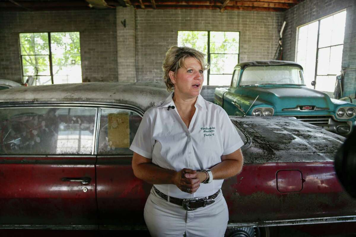 In this Aug. 12, 2013 photo, auctioneer Yvette VanDerBrink stands in front of a brand new, old 1963 Chevrolet Impala and a brand new, old 1958 Cameo pickup truck, right, at the former Lambrecht Chevrolet car dealership in Pierce, Neb. Next month, bidders from at least a dozen countries and all 50 U.S. states will converge on Pierce, a town of about 1,800 in northeast Nebraska, for a two-day auction that will feature about 500 old cars and trucks, mostly Chevrolets that went unsold during the dealership's five decades in business. About 50 have fewer than 20 miles on the odometer, and some are so rare that no one has established a price. The most valuable could fetch six-figure bids.