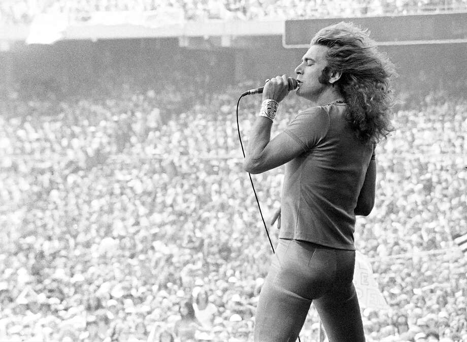 "Robert Plant performing on stage, wearing a ""Nurses do it Better"" t-shirt, at the Oakland Coliseum. Photo: Ed Perlstein, Redferns / Redferns"