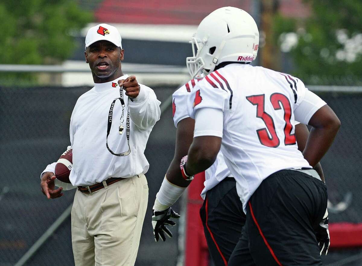 Louisville head football coach Charlie Strong, left, shouts instructions to running back Senorise Perry during the first day of NCAA college football practice on Tuesday, Aug. 6, 2013 in Louisville, Ky. (AP Photo/Timothy D. Easley)
