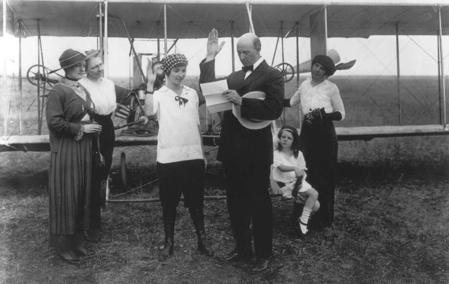 A 19-year-old Marjorie Stinson is shown taking her oath as a mail carrier on May 4, 1915, from San Antonio postmaster George D. Armistead in this file photograph provided by the Institute of Texan Cultures. Stinson's route between Seguin and San Antonio made her the first flying mail carrier in Texas. Photo: FILE / INSTITUTE OF TEXAN CULTURES FILE