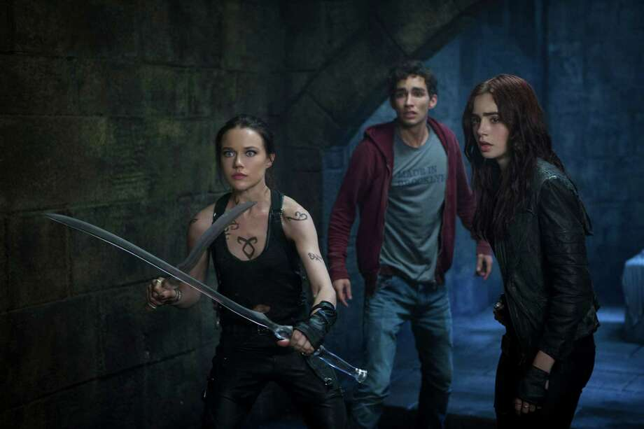 Rafy/Screen Gems Isabelle Lightwood (Jemima West), Simon (Robert Sheehan) and Clary (Lily Collins) prepare to hold off the demons in Screen Gems THE MORTAL INSTRUMENTS: CITY OF BONES. Photo: Rafy / © 2013 Constantin Film International GmbH and Unique Features (TMI) Inc. All rights reserved.  **ALL IMAGES ARE PROPERTY OF SON