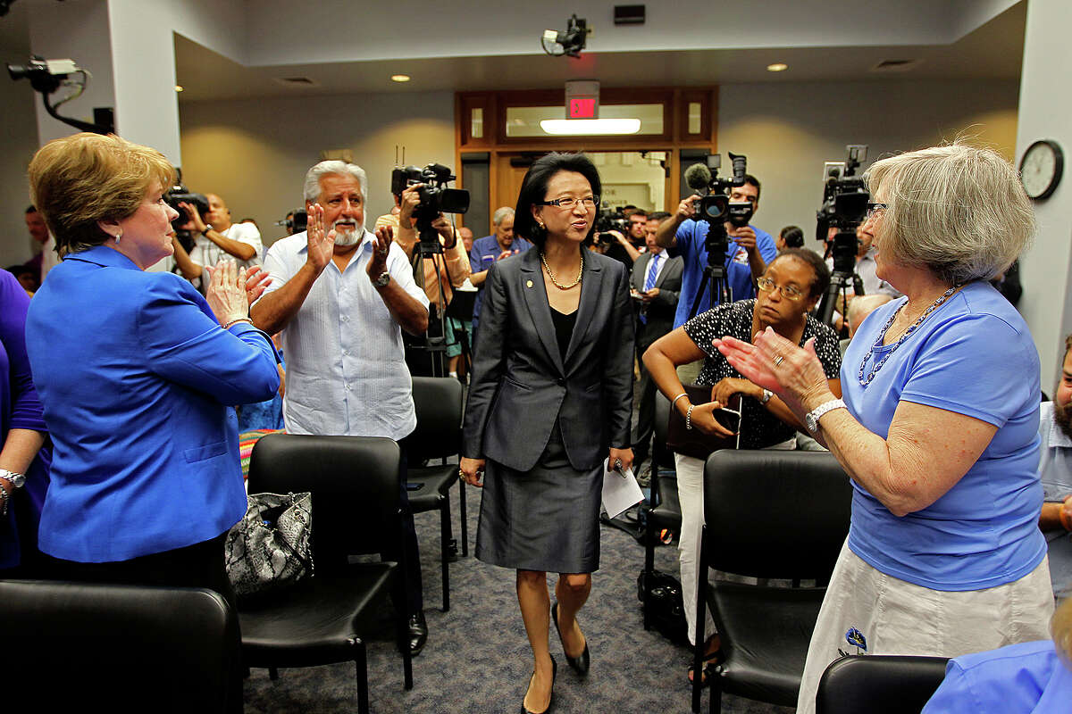 Supporters greet San Antonio City Councilwoman District 9 Elisa Chan as she enters a briefing room for a press conference at City Hall, Tuesday, Aug. 20, 2013. In a secret recording by former staff member James Stevens on May 21, Chan condemned homosexuality and described it as