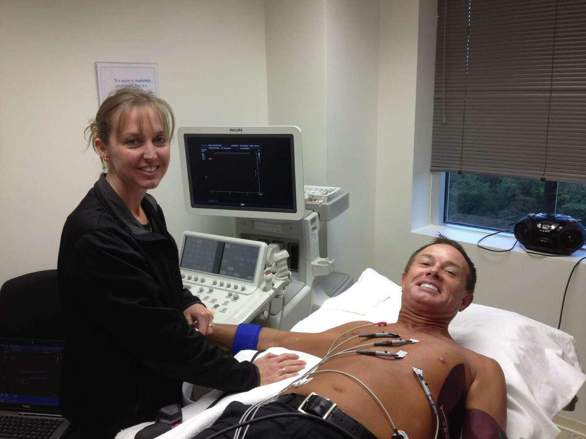 University of Texas staffer Nikki Herrin measures the effect of an energy drink on Dr. John Higgins' heart.