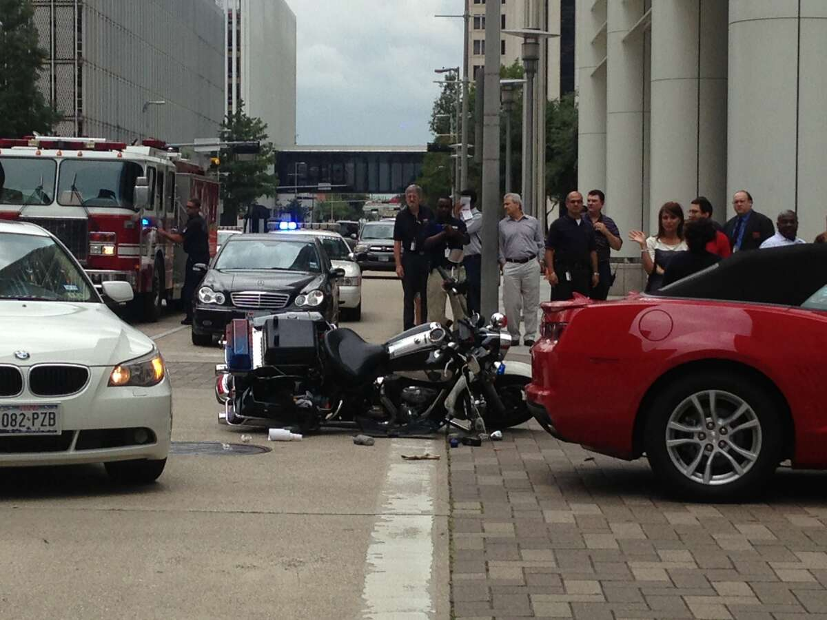 A Houston police officer wrecked his motorcycle at Bell and Louisiana in downtown Houston, Aug. 20. (James Nielsen / Houston Chronicle)