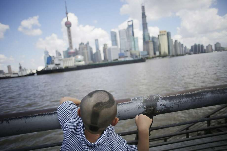 The 'why?' stage:A little boy with a partially shaved head searches for answers in the skyline of Pudong, China's financial and commercial hub in Shanghai. Photo: Eugene Hoshiko, Associated Press