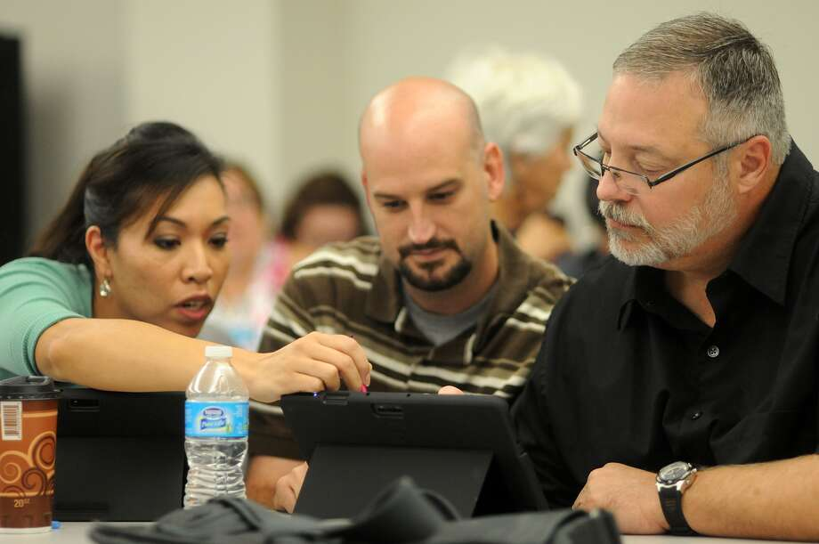 Christina Davidson, left, Christopher Taylor and Bret Ewing, all eighth-grade science teachers at Victory Lakes Intermediate, brainstorm during an Aug. 8 computer tablet training session at Clear Creek Independent School District Technology Learning Center. Christina Davidson, left, Christopher Taylor and Bret Ewing, all eighth-grade science teachers at Victory Lakes Intermediate, brainstorm during an Aug. 8 computer tablet training session at Clear Creek Independent School District Technology Learning Center. Photo: Jerry Baker, Freelance