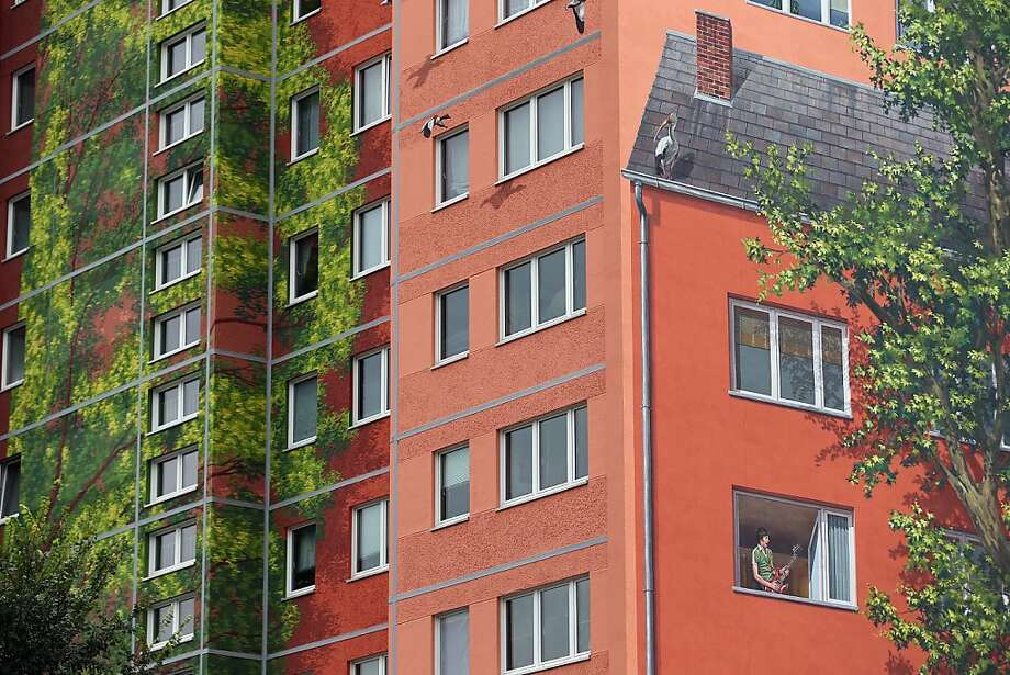 Wall of sound:The musician in 304 is always playing his guitar in this trompe l'oeil mural on one of the Wohngenossenschaft Soldaritaet co-op apartment buildings in Berlin. A group of artists working for French-based Citecreation painted the facades of the three buildings in imagery inspired by a nearby zoo. Residents approved of the art, which Citecreation hopes will be recognized by Guinness as the largest mural on an inhabited structure in the world. Photo: Sean Gallup, Getty Images