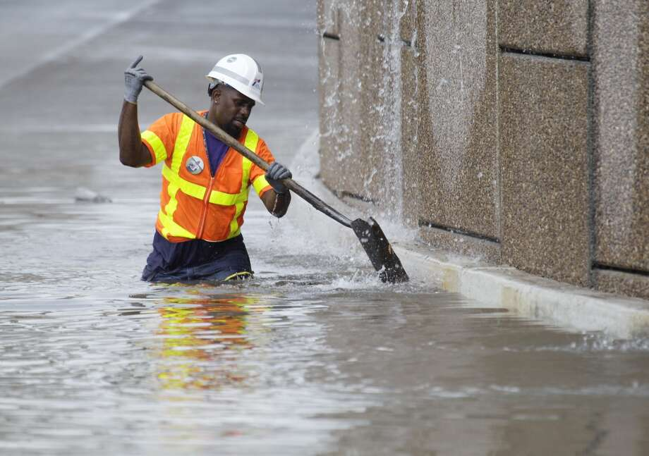 TxDOT worker Rodgerick Whitetries to clear debris along flooded section of Providence St. along I-10 near Jensen Tuesday, Aug.  20, 2013. ( Melissa Phillip / Houston Chronicle)