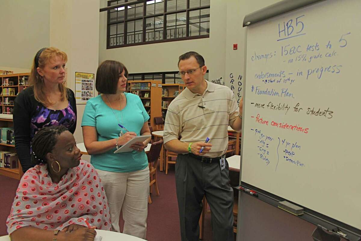 Anthony Indelicato, principal, Kempner High School, discusses graduation changes with counselors Erin Swanson, standing left, and Kerry Jongeward, and Renee Edwards, seated.