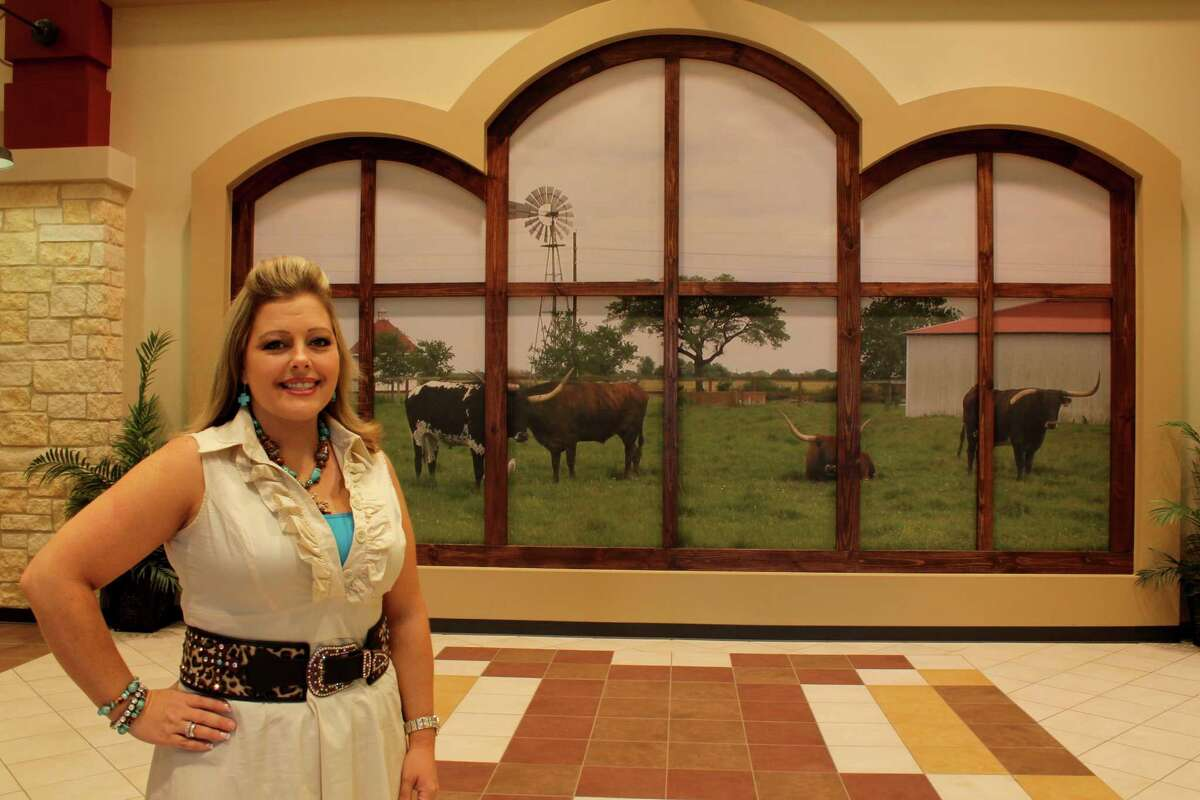 Heather Patterson, principal of the new Polly Ryon Middle School at 7901 FM 762 in Richmond, stands beside a photographic mural of the longhorn cattle that graze at the George Ranch. The mural covers the wall at the entrance of the new school.
