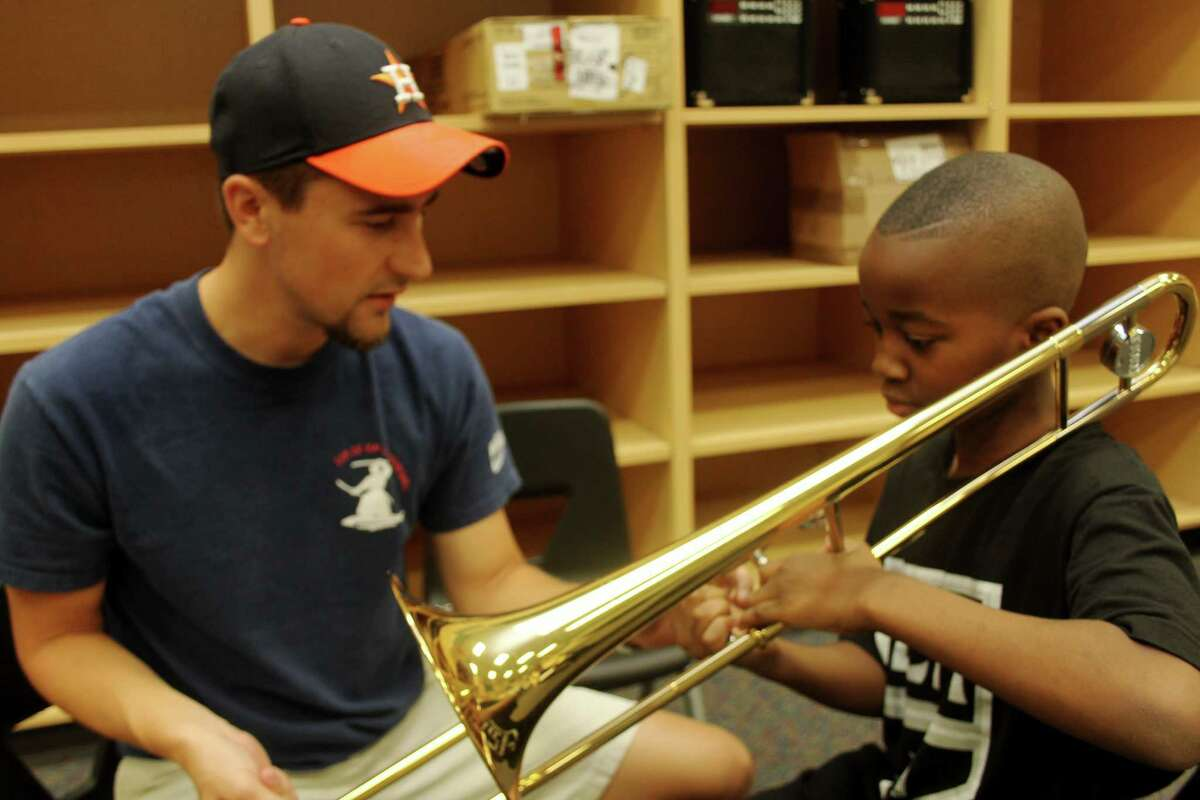 Thomas Piazza, band director at Polly Ryon Middle School at 7901 FM 362 in Richmond, shows new student, Promise Eke, 10, of Sugar Land how to hold a trombone, the instrument he has selected to play.