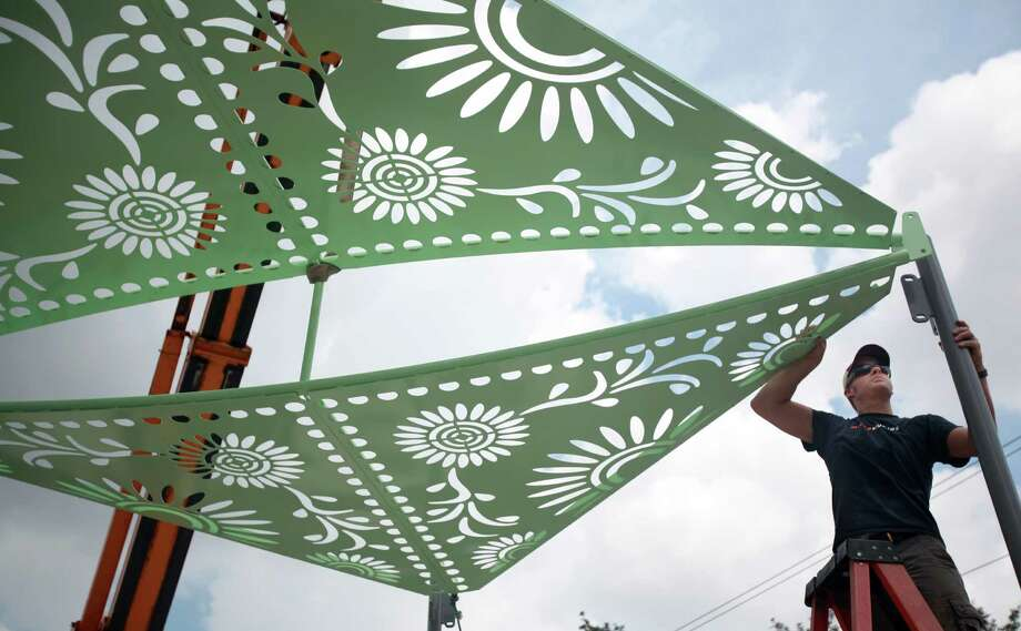 Matt Schott helps install a colorful canopy at the Navigation Boulevard Esplanade. Photo: Mayra Beltran, Houston Chronicle / © 2013 Houston Chronicle