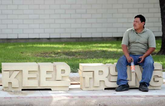 Jose Escobar sits on street art placed at the bus stop as part of the Navigation Boulevard Esplanade. Photo: Mayra Beltran, Houston Chronicle / © 2013 Houston Chronicle