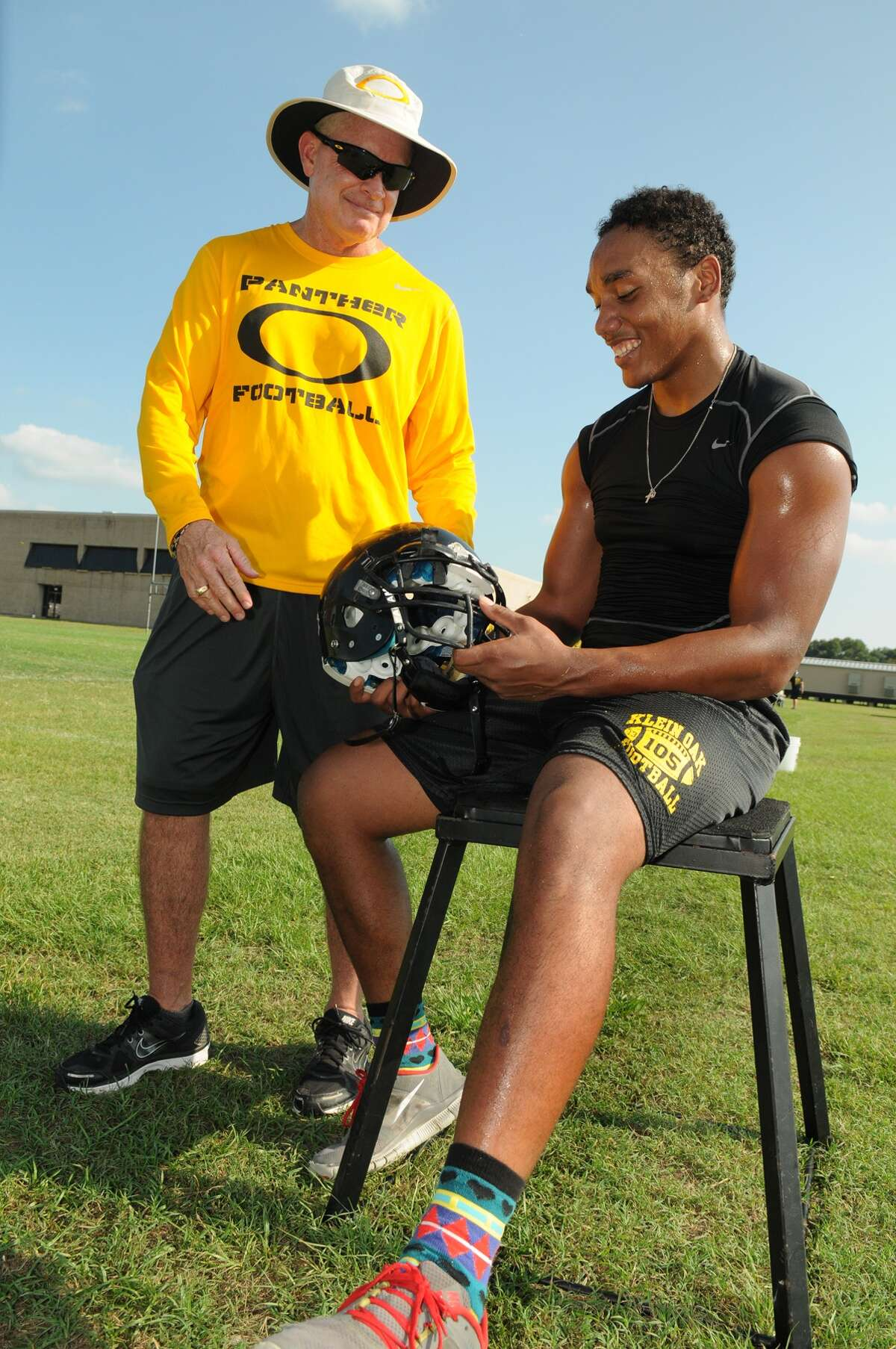Klein Oak head coach David Smith, from left, chats with senior linebacker Josh Mabin during a team practice last week.