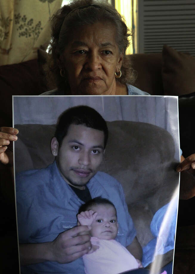 Stella Lopez holds a photograph Tuesday August 20, 2013 of her grandson Gilbert Ramos,25. Ramos was killed last Saturday night at the intersection of of Wallace street and General McMullen when a man  fleeing from a different accident struck and killed Ramos. Jose Hernandez,56, has been charged with intoxication manslaughter after allegedly striking Ramos while Ramos was crossing the street. Hernandez has been convicted of driving while intoxicated four times since 1984. The little girl being held by Ramos is his daughter Azeriyah Huichan,1. Photo: JOHN DAVENPORT, SAN ANTONIO EXPRESS-NEWS / ©San Antonio Express-News/Photo may be sold to the public