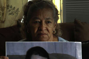 Stella Lopez holds a photograph Tuesday August 20, 2013 of her grandson Gilbert Ramos,25. Ramos was killed last Saturday night at the intersection of of Wallace street and General McMullen when a man  fleeing from a different accident struck and killed Ramos. Jose Hernandez,56, has been charged with intoxication manslaughter after allegedly striking Ramos while Ramos was crossing the street. Hernandez has been convicted of driving while intoxicated four times since 1984. The little girl being held by Ramos is his daughter Azeriyah Huichan,1.