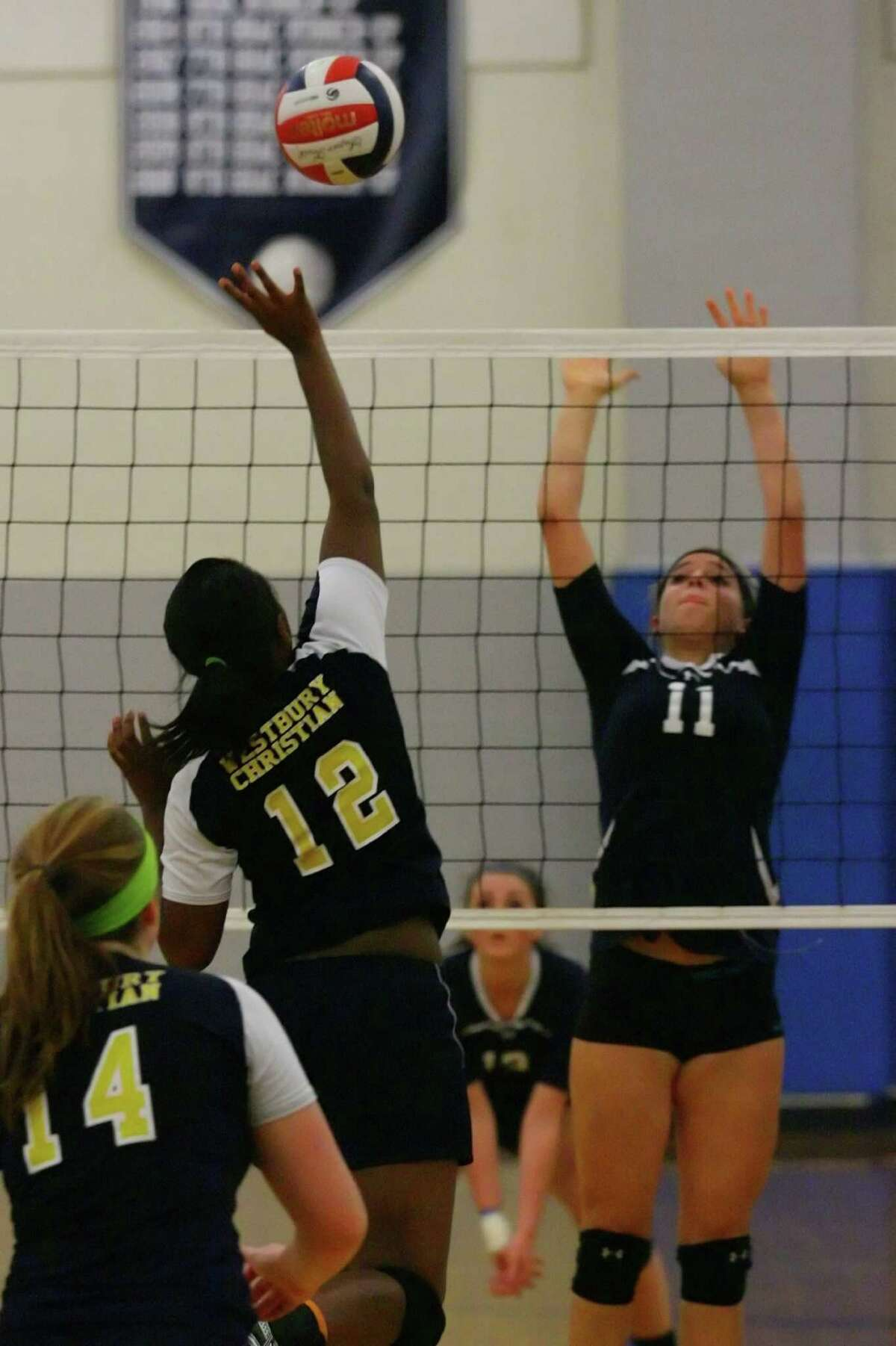 Simone Edwards of Westbury Christian takes her shot as she is challenged by Megan Sheena of Emery at the net.