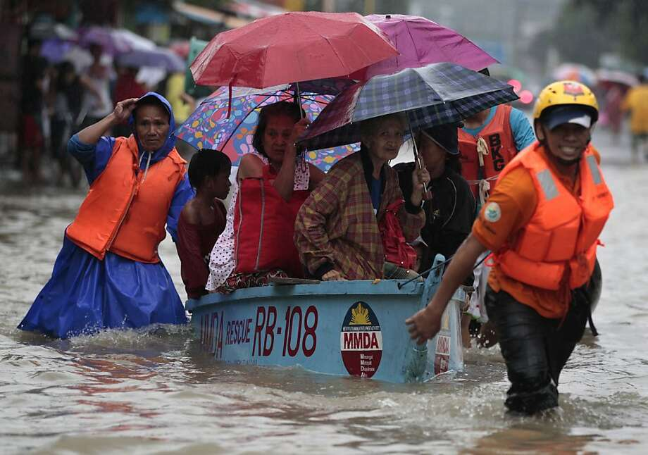 Rescuers pull a boat carrying residents as they enforce evacuation at an area flooded due to a swollen river in Marikina city, east of Manila, Philippines Tuesday, Aug. 20, 2013. Some of the Philippines' heaviest rains on record fell for a second day Tuesday, turning the capital's roads into rivers and trapping tens of thousands of people in homes and shelters. The government suspended all work except rescues and disaster response. (AP Photo/Aaron Favila) Photo: Aaron Favila, Associated Press