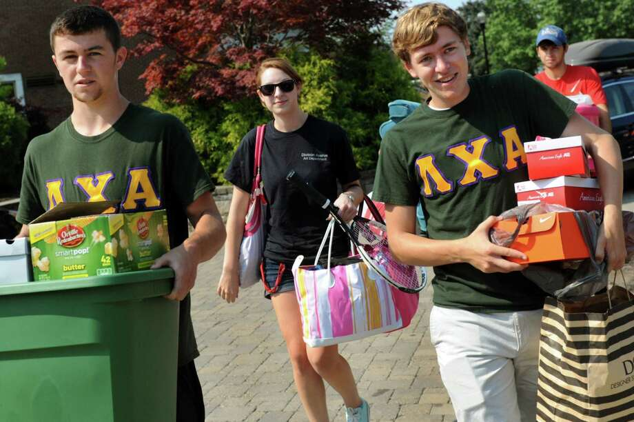 Freshman Theresa Winkler, 18, of Long Island, center, gets help moving into Barton Hall on Tuesday, Aug. 20, 2013, at Rensselaer Polytechnic Institute in Troy, N.Y. Assisting her are Lambda Chi Alpha fraternity brothers Zach Wolfgang, 18, left, and Chris Volk, 21, right. (Cindy Schultz / Times Union) Photo: Cindy Schultz / 00023564A