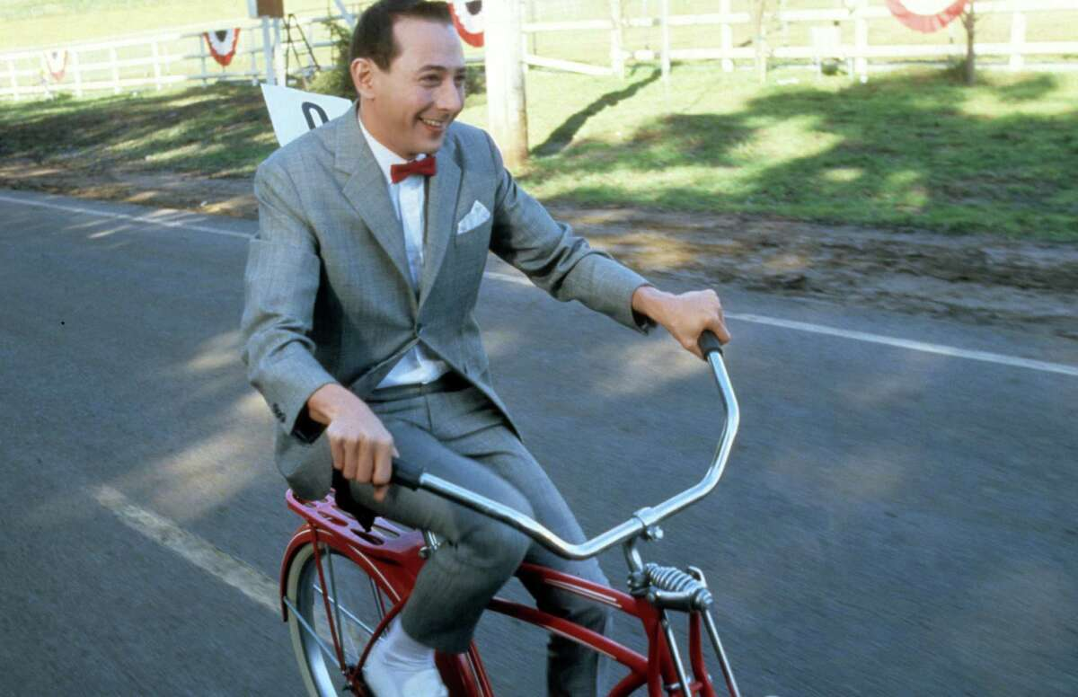 """Paul Reubens rides a bike in a scene from the 1985 film """"Pee-Wee's Big Adventure."""""""