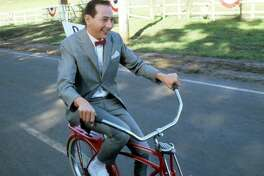 Paul Reubens rides a bike in a scene from the film 'Pee-Wee's Big Adventure', 1985.