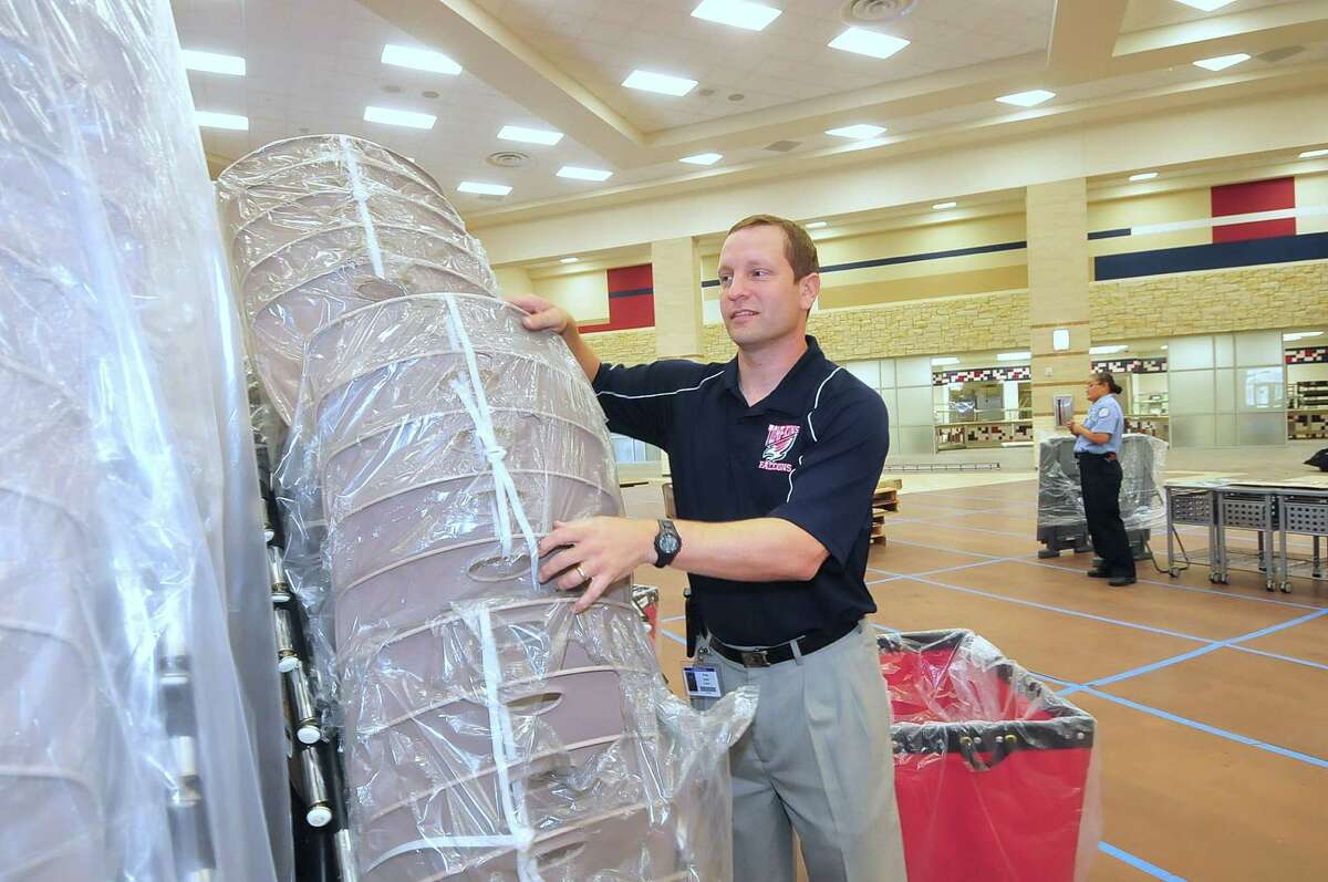 Ryan Labay, associate principal, helps unwrap chairs Aug. 6 in the auditorium at the new Tompkins High School in the Katy Independent School District.Ryan Labay, associate principal, helps unwrap chairs Aug. 6 in the auditorium at the new Tompkins High School in the Katy Independent School District.
