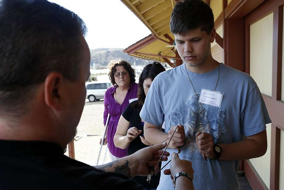 Benicia Ghost Conference tour leader Devin Sisk shows Justin Ferrell how to use dowsing rods to sense the paranormal. Photo: Ian C. Bates, The Chronicle