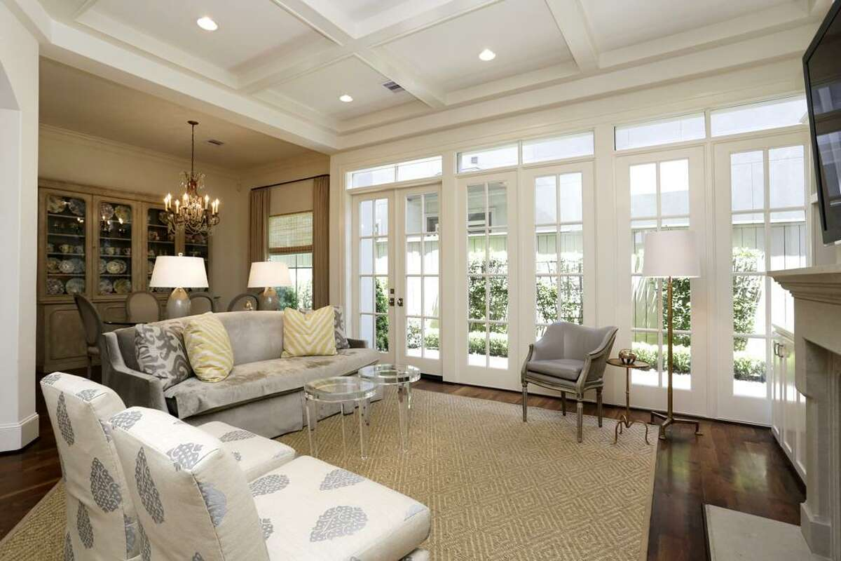 The den area provides spaciousness as it blends with the formal dining area. A set of glass French doors offers natural light to flow into the space.