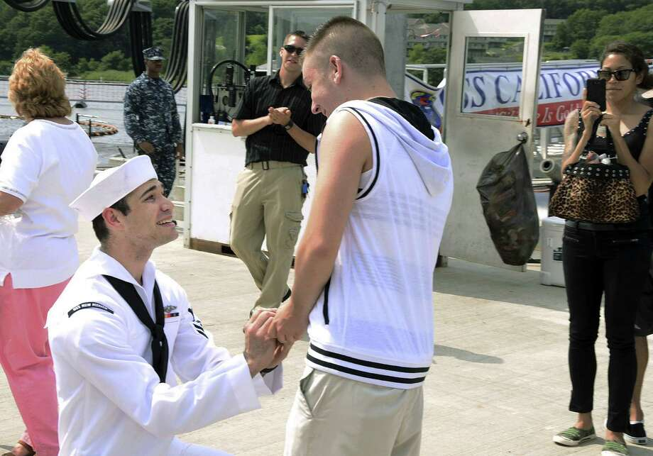 Petty Officer 2nd Class Jerrel Revel, left, proposes to his boyfriend Dylan Kirchner Aug. 12 during the homecoming of the USS New Mexico at the submarine base in Groton, Conn. Defense officials estimate there are 18,000 same-sex couples in the active-duty military, National Guard and Reserves. It's unclear how many of those are married.