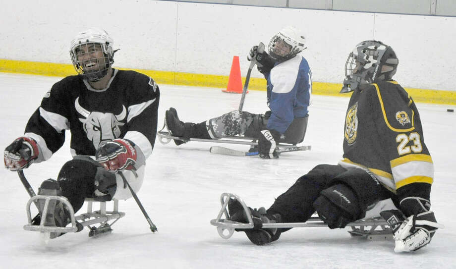 San Antonio Rampage sled hockey defenseman Rico Roman (left) scores a goal on the Rampage's goaltender, Jen Yung Lee (right) July 31. Roman, Lee and Joseph Sweeney (not shown), will represent Team USA at the 2014 Paralympic Winter Games.
