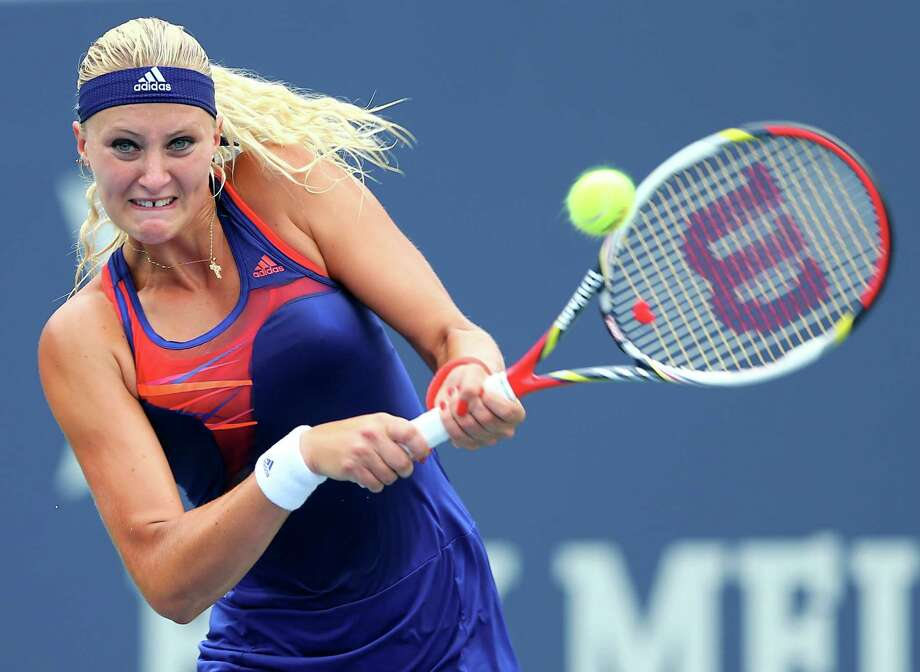 NEW HAVEN, CT - AUGUST 18:  Kristina Mladenovic of France returns a shot to Sabine Lisicki of Germany during Day One of the New Haven Open at Connecticut Tennis Center at Yale on August 18, 2013 in New Haven, Connecticut. Photo: Elsa, Getty Images / 2013 Getty Images