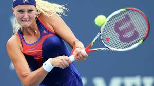 NEW HAVEN, CT - AUGUST 18:  Kristina Mladenovic of France returns a shot to Sabine Lisicki of Germany during Day One of the New Haven Open at Connecticut Tennis Center at Yale on August 18, 2013 in New Haven, Connecticut.