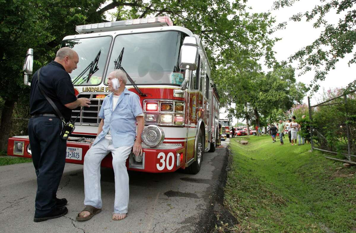 Houston firefighter A. Goebel, left, talks with a resident who escaped a house fire in the 4700 block of Sharman near Calvalcade Tuesday, Aug. 20, 2013, in Houston. He said the man's face was bandaged previous to the fire.