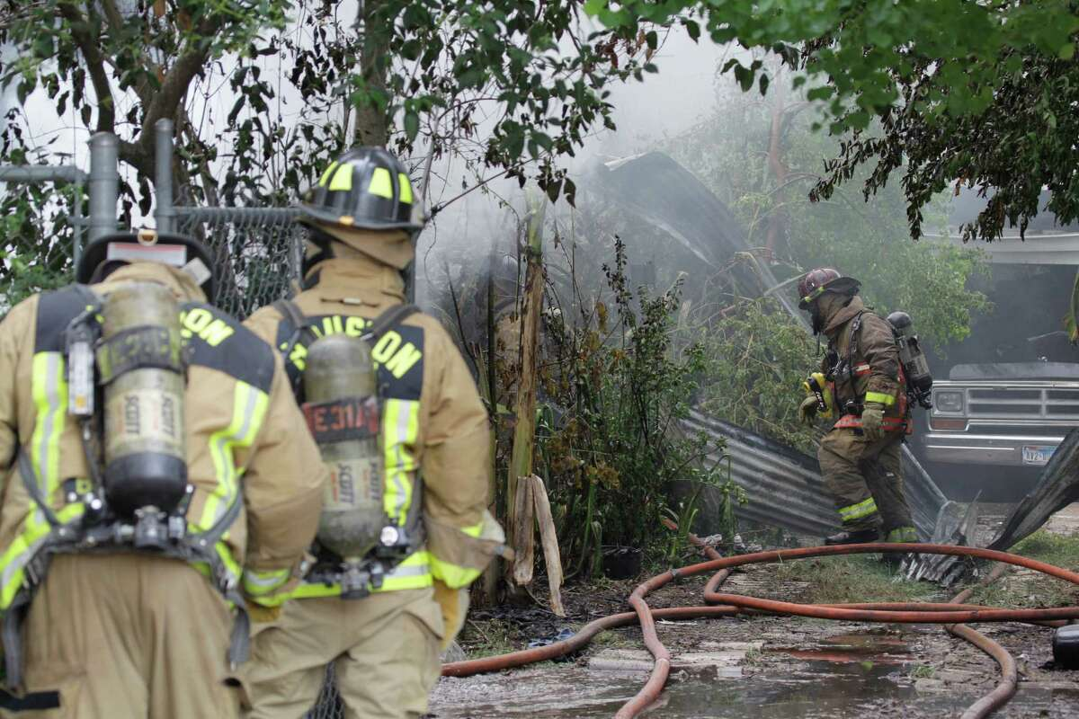 Houston firefighters battle a house fire in the 4700 block of Sharman near Calvalcade Tuesday, Aug. 20, 2013, in Houston.