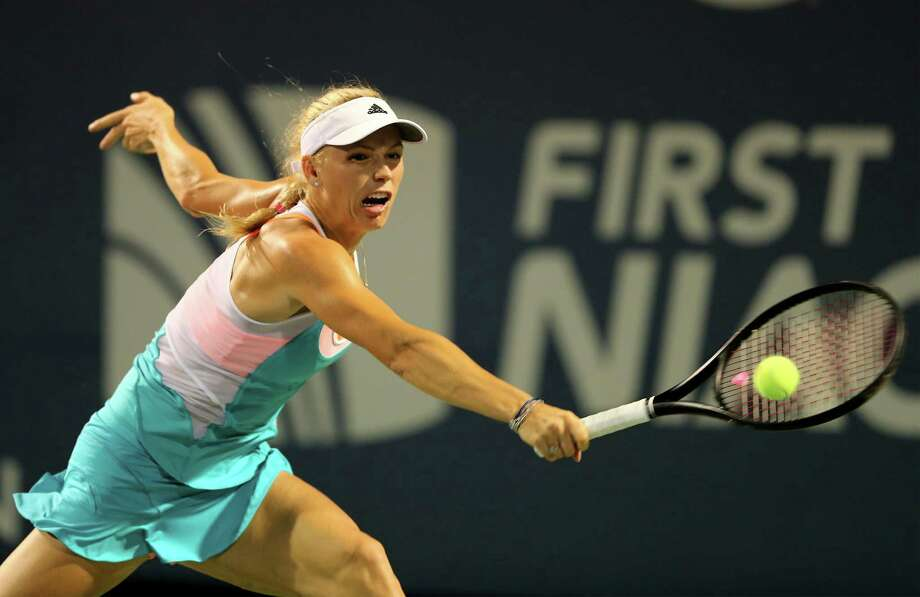 NEW HAVEN, CT - AUGUST 19:  Caroline Wozniacki of Denmark returns a shot to Shuai Peng of China in the first set during Day Two of the New Haven Open at the Connecticut Tennis Center at Yale on August 19, 2013 in New Haven, Connecticut. Photo: Elsa, Getty Images / 2013 Getty Images