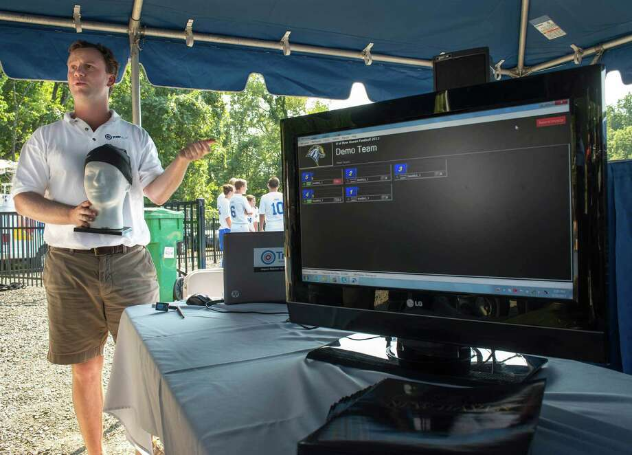 Chad Hollingsworth of TRIAX Technologies demonstrates their wireless sensors that monitors the head impact of athletes during play. He is holding a mannequin head that has a skullcap that has one of their SIM's (Smart Impact Monitors) built into it. The computer screen shows the numbers of the players wearing the device and will show the g-force of the impact of a hit to their head. University of New Haven soccer and football players wore the devices during a demonstration held at the Ralph F. DellaCamera stadium at the university in West Haven, CT on Tuesday August 20th, 2013. Photo: Mark Conrad / Connecticut Post Freelance