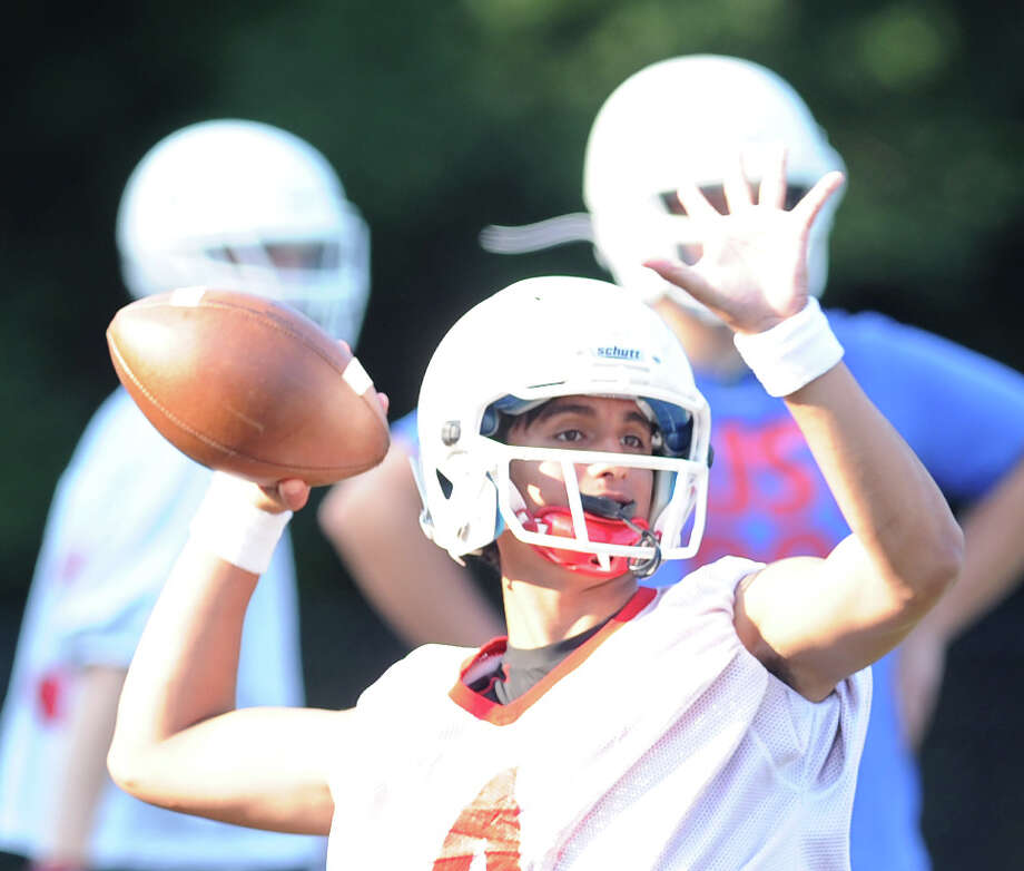 Greenwich High School quarterback Jose Melo throws during football practice at Cardinal Stadium, Tuesday night, August 20, 2013. Photo: Bob Luckey / Greenwich Time