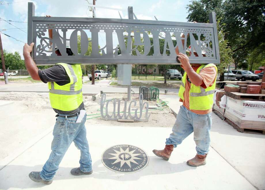 Workers install street art signs to their final location along the Navigation Boulevard Esplanade on Tuesday, Aug. 20, 2013, in Houston. The esplanade along Navigation Boulevard between N. St. Charles Street and N. Paige Street is meant to be an attraction for local residents and tourists of the East End. Photo: Mayra Beltran, Houston Chronicle / © 2013 Houston Chronicle