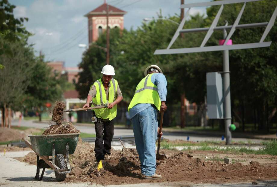 Juan Gonzalez and John Mullen work on the landscaping along the Navigation Boulevard Esplanade. Photo: Mayra Beltran, Houston Chronicle / © 2013 Houston Chronicle
