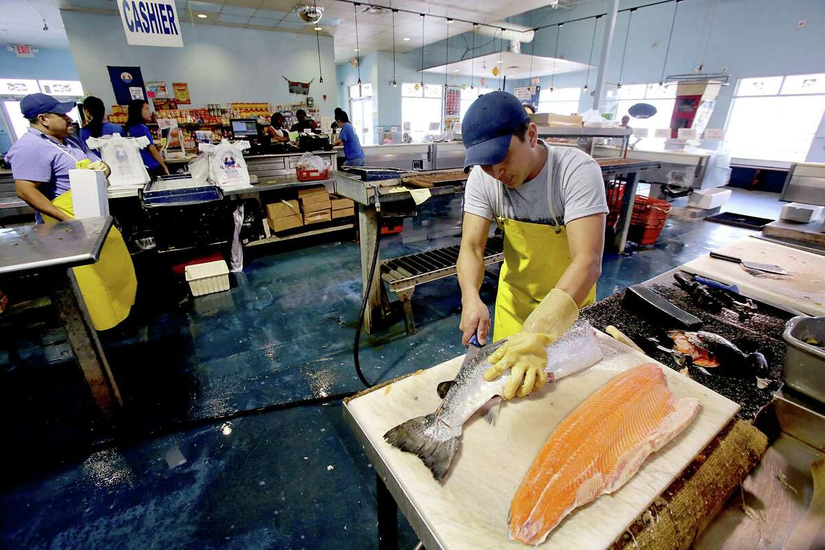 Roses Seafood, located at the intersection of Waterfront and Bath, is one of the business that has been rebuilt in Seabrook, Texas. Michael Gilberto cuts up Scottish Salmon.
